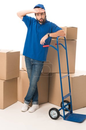 tired delivery man standing between cardboard boxes isolated on white