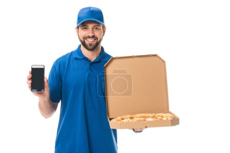 handsome delivery man holding smartphone and pizza in box isolated on white