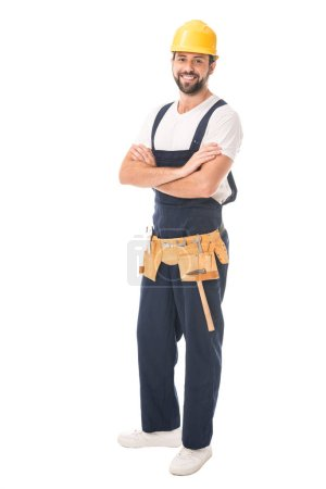 full length view of handsome happy workman in hard hat and tool belt standing with crossed arms and smiling at camera isolated on white