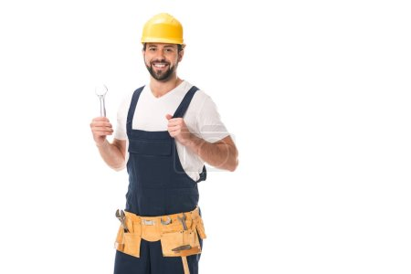 happy workman holding wrench and smiling at camera isolated on white