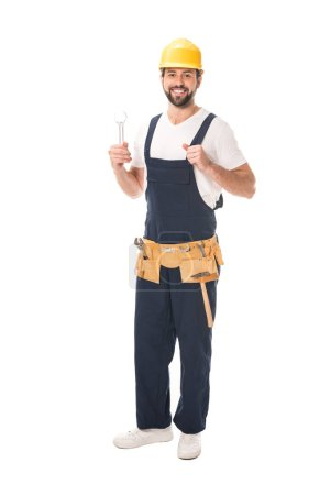 handsome happy workman holding wrench and smiling at camera isolated on white