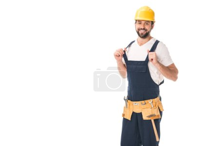 handsome happy workman in tool belt and hard hat smiling at camera isolated on white