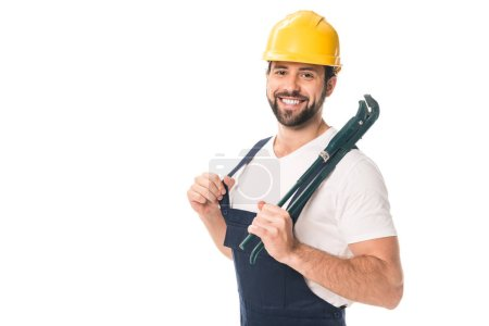 handsome happy workman holding adjustable wrench and smiling at camera isolated on white