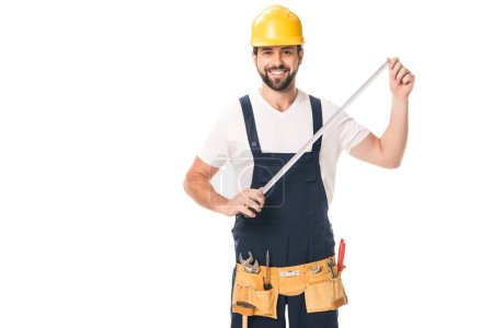 handsome happy workman holding measuring tape and smiling at camera isolated on white