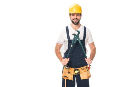handsome happy repairman in tool belt holding adjustable wrench and smiling at camera isolated on white