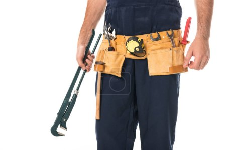 cropped shot of repairman in tool belt holding adjustable wrench isolated on white