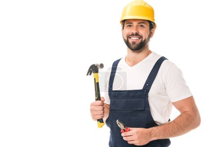 handsome smiling workman holding pliers and hammer isolated on white