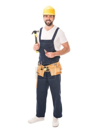 full length view of handsome repairman holding tools and smiling at camera isolated on white
