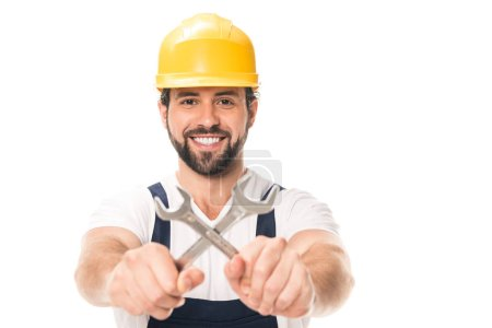Photo for Handsome repairman holding wrenches and smiling at camera isolated on white - Royalty Free Image