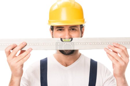 handsome construction worker in hard hat holding level tool and looking at camera isolated on white
