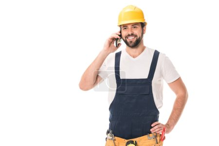 happy handsome construction worker in hard hat talking by smartphone isolated on white