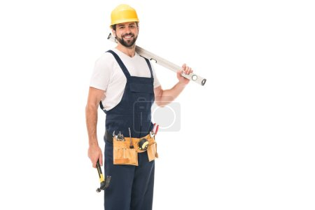 handsome happy workman holding level tool and hammer, smiling at camera isolated on white