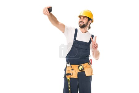 happy handsome workman in hard hat and tool belt taking selfie with smartphone isolated on white