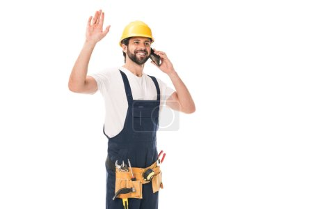 cheerful construction worker talking by smartphone and waving hand isolated on white
