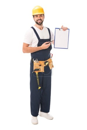 handsome construction worker in tool belt holding blank clipboard and smiling at camera isolated on white