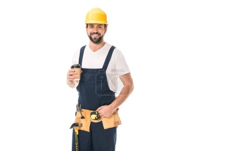 handsome happy workman in tool belt holding paper cup with coffee to go and smiling at camera isolated on white