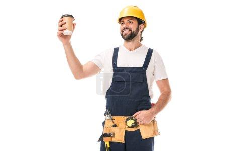 Photo pour Beau ouvrier heureux dans la ceinture d'outil tenant la tasse de papier avec le café pour aller isolé sur blanc - image libre de droit