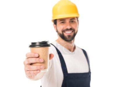 Photo pour Vue rapprochée d'un travailleur heureux dans un casque, tenant la tasse de papier avec le café pour aller et souriant à la caméra isolé sur blanc - image libre de droit