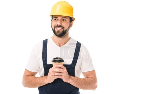 handsome smiling workman in hard hat holding coffee to go and looking away isolated on white