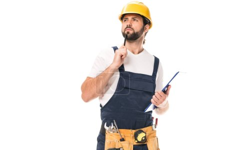 pensive construction worker with tool belt holding clipboard and looking away isolated on white