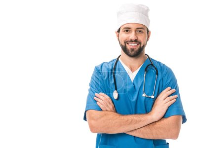 handsome bearded surgeon standing with crossed arms and smiling at camera isolated on white