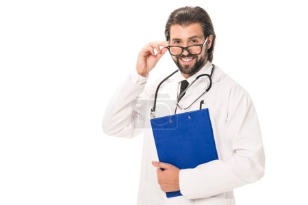 doctor with clipboard adjusting eyeglasses and smiling at camera isolated on white