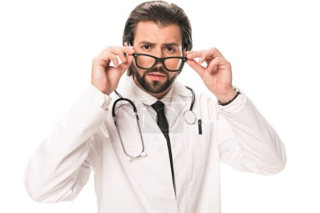 bearded doctor in white coat adjusting eyeglasses and looking at camera isolated on white
