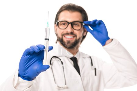 close-up view of smiling doctor in medical gloves holding syringe isolated on white