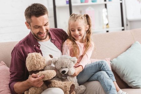 father and daughter playing with teddy bears on father knees