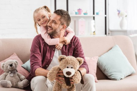 daughter hugging father on sofa with teddy bears at home