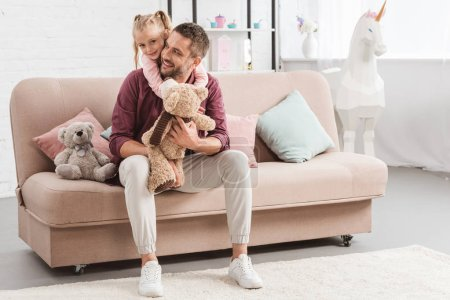 daughter hugging father on sofa with toys at home