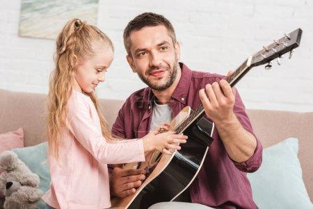 Foto de Padre e hija divirtiéndose y jugando en la guitarra en el sofá - Imagen libre de derechos