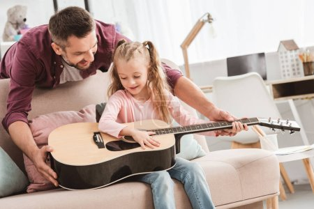 father and daughter playing on guitar at home