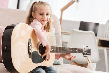 smiling kid playing on guitar at home
