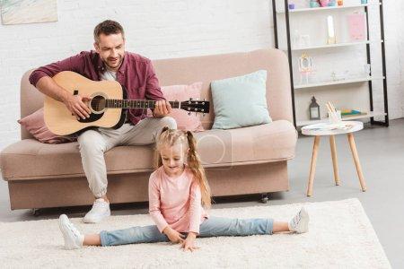 Foto de Dad de heerful tocando en la guitarra mientras que hija haciendo split en planta - Imagen libre de derechos