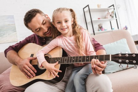 dad and daughter having fun and playing on guitar