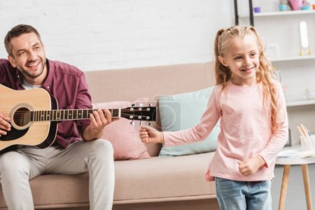 happy daughter dancing while father playing on guitar