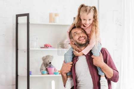 daughter sitting on fathers shoulders and hugging at home
