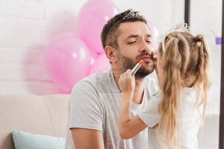 daughter doing makeup with lipstick to father