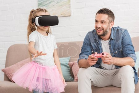 happy father and daughter playing with joystick and virtual reality headset at home