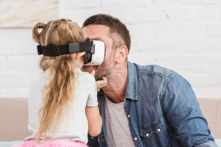 father and smiling daughter using virtual reality headset together at home