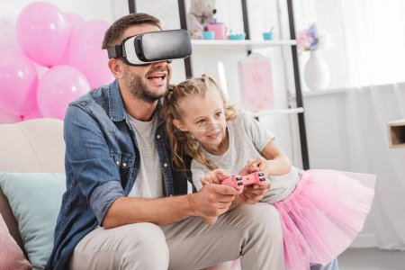 cheerful dad and daughter having fun and playing with joystick and using virtual reality headset on sofa