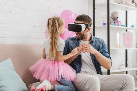 father and daughter having fun and using virtual reality headset on sofa
