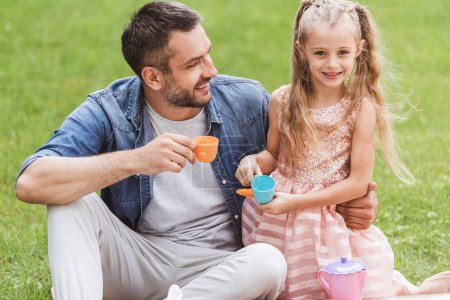 father and daughter playing tea party at lawn
