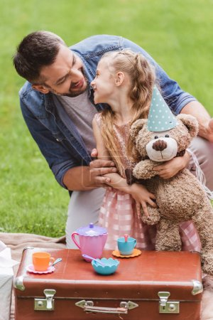 father and daughter with teddy bear playing tea party at lawn