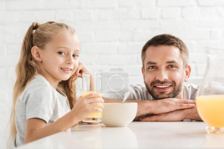 father and daughter drinking orange juice and looking at camera