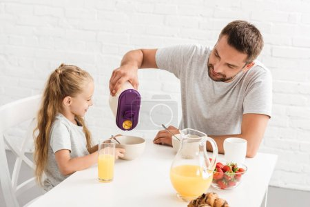 Photo for Father and daughter eating cornflakes at kitchen - Royalty Free Image