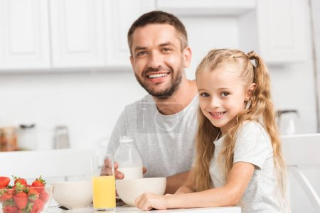 father and daughter having breakfast and looking at camera