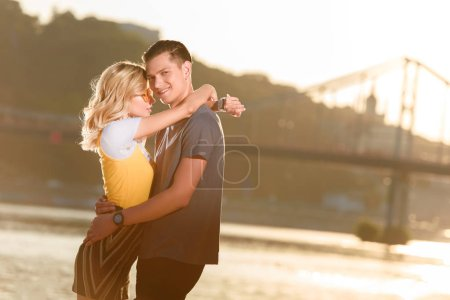 side view of young couple hugging on river beach in evening