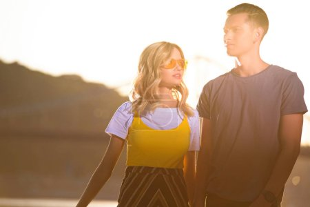 young couple standing on river beach during sunset